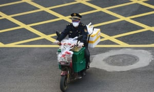 An official rides a bike filled with food supplies in Wuhan on Monday.