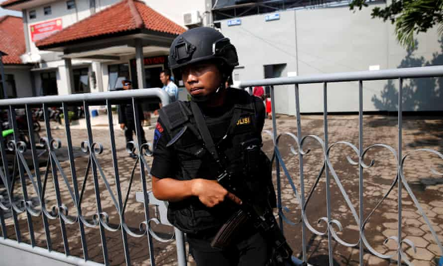 An armed police officer at the gate to the ferry port for the prison island of Nusa Kambangan in Cilacap, Indonesia.