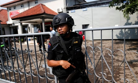 An armed police officer outside the gate to the ferry port for the prison island of Nusa Kambangan.