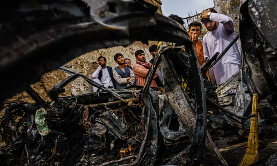 People gathered around the incinerated husk of a vehicle targeted by a US drone strike, which killed 10 people including children, in Kabul, Afghanistan, 30 August 2021.