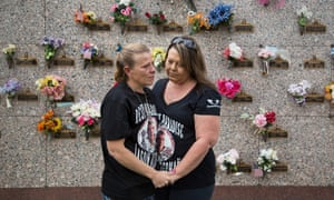 The mother and aunt of Jason Alderman stand in front of his gravesite in Bakersfield, California.