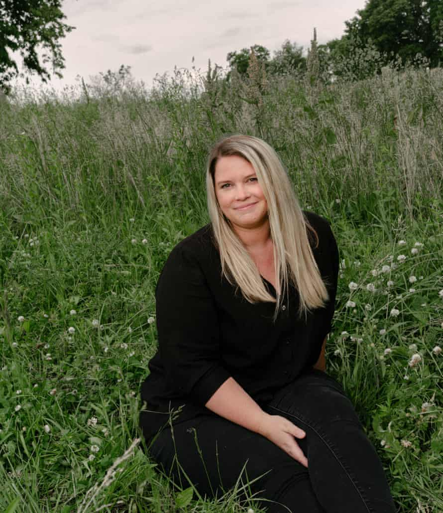 Kate Baer dressed in black sitting in a field