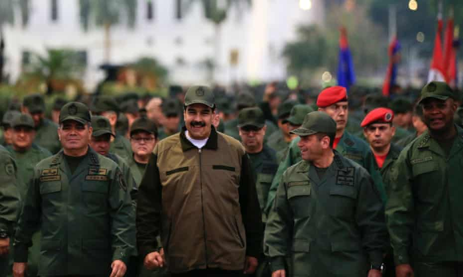 Venezuela's President Nicolás Maduro is accompanied by the defence minister, Vladimir Padrino, left, and a large body of loyal troops in Caracas on Thursday.