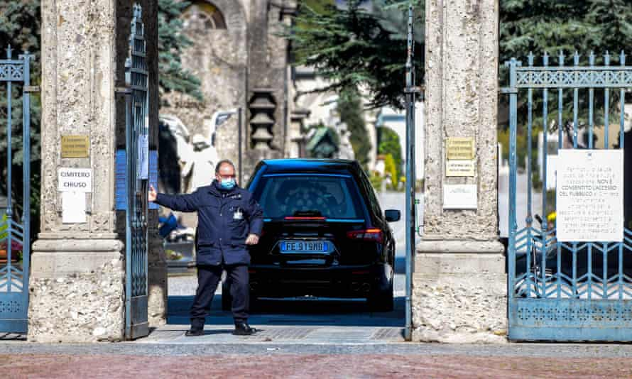 A cemetery employee closes the gates behind a hearse at the Monumental cemetery of Bergamo