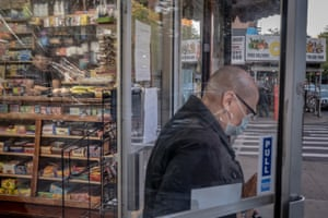 A woman exits a newly reopened convenient store in Brooklyn, New York on Thursday, May 21st.