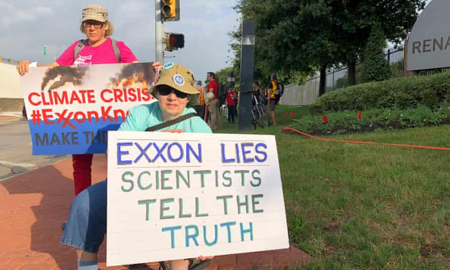 Blanca Gonzales, left, and Susan Cooper protest ExxonMobil's climate change policies in Dallas.