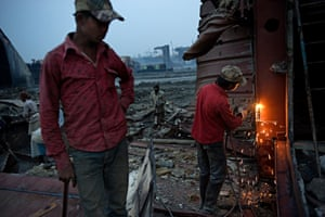 Laborers on Chittagong beach use blowtorches to disassemble parts of a mega freighter.