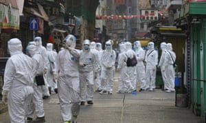 Government investigators wearing protective suits gather in the Yau Ma Tei area in Hong Kong, where thousands of residents have been locked down