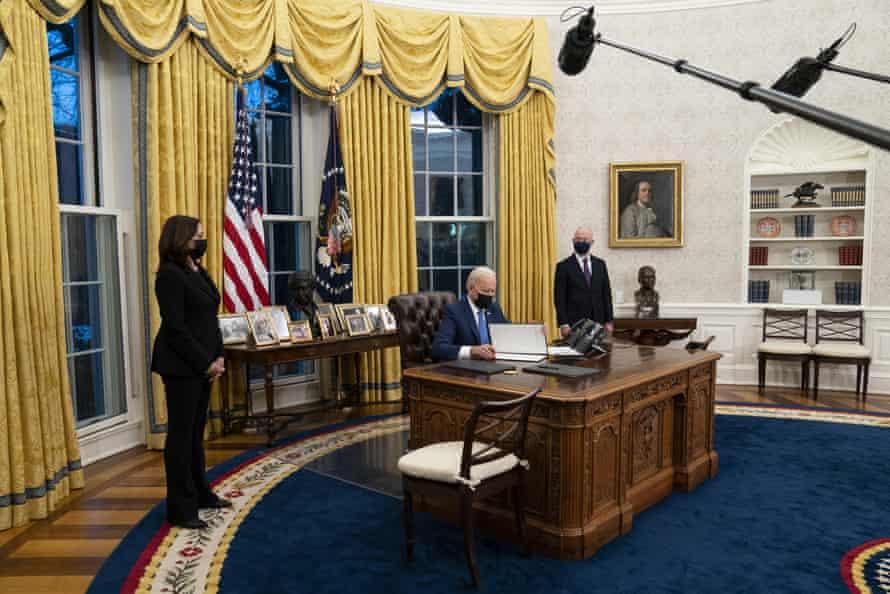 Vice-President Kamala Harris, left, and Alejandro Mayorkas, the homeland security secretary, look on as President Joe Biden signs an executive order on immigration.