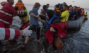 Refugees land on the beach near the village of Sikaminias on the Greek island of Lesvos and are helped by volunteers. Photograph: Sean Smith