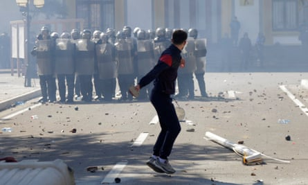 An anti-government protester throws a rock at police in Albanian capital Tirana.