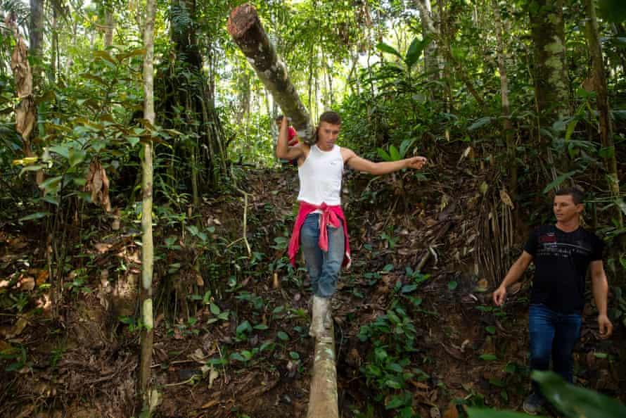Dionio Araujo Guimarães creates a bridge over a watery ditch on the rubber trail.