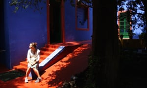 A visitor sits in the courtyard of the Frida Kahlo Museum.