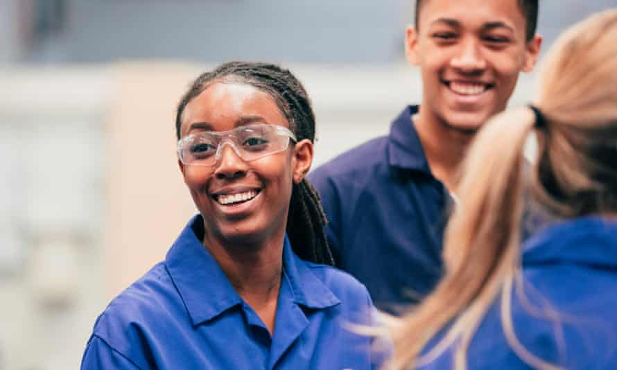 .A young black woman, who is wearing protective eyewear, smiles as she enjoys her engineering class with her peers - they are all wearing blue coveralls.