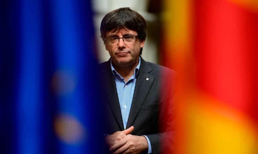 Catalan president Carles Puigdemont poses between an EU and a Catalan flag.