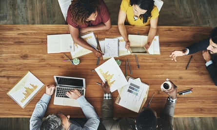 High angle shot of a team of businesspeople meeting around the boardroom table in the office.