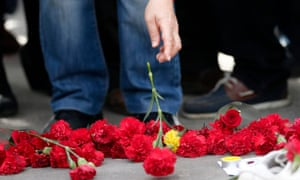 People place flowers on the ground to commemorate the victims of a bombing in Ankara, October 2015