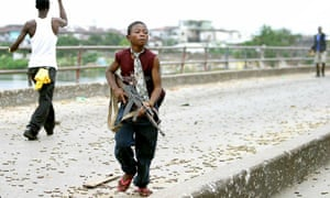A Liberian child soldier fights in Monrovia, Liberia 30 July 2003. The Covid-19 pandemic could force more children into conflict.