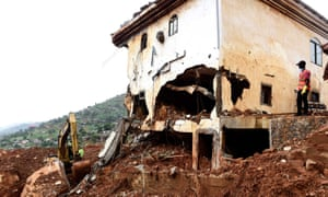 A man looks on as a digger is used to clear mud and debris from a partially collapsed hillside in Freetown