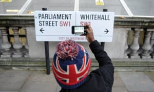 A tourist photographing the Parliament Street/ Whitehall sign, London.