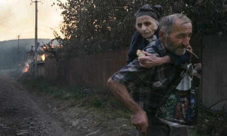 Georgians flee a house set on fire by South Ossetian militia