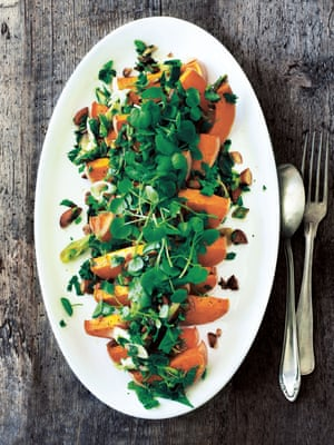 Orange butternut squash slices, topped with watercress on a white oval plate.