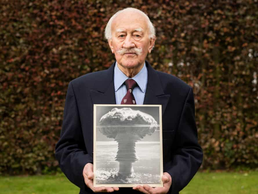 Alan Pringle holding a photo of a nuclear explosion