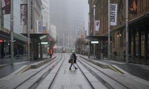 A pedestrian wearing a protective face mask walks past light rail platforms devoid of waiting passengers in the city centre at morning commute hour in Sydney, Australia, 30 June 2021.