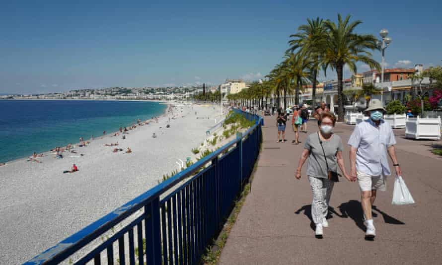 People wearing face masks walk along the Promenade des Anglais in Nice, France.