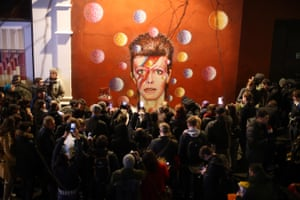 Members of the media and public gather by a mural of David Bowie in Brixton on 11 January