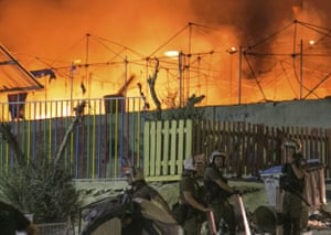 Riot police stand guard as a large fire burns inside the Moria refugee camp last September