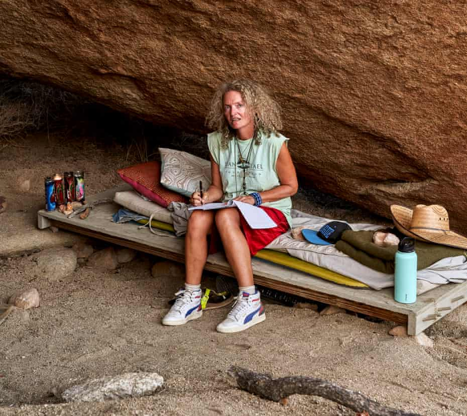 Stephanie Theobald sits on her bed – a board balanced on stones – in her cave.