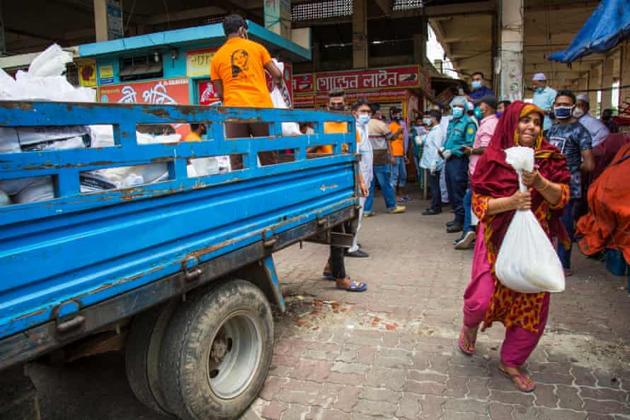 A woman walks away from a food-relief truck with a sack of produce