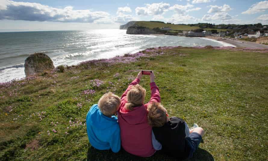 A family take a selfie by the coast