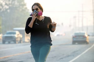 A woman covers her face as she runs along Sierra Highway in southern California.