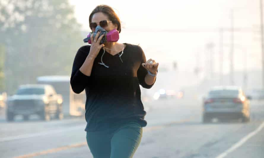 A woman covers her face as she run along Sierra Highway as the Tick fire burns in Canyon Country.