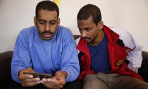 Kotey, left, and Elsheikh, read a news article about themselves during an interview with The Associated Press at a security center in Kobani, Syria in 2018.