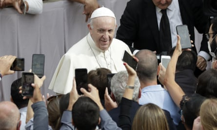 People hold up their phones and crowd towards Pope Francis