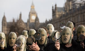 Protesters outside Westminster with Theresa May masks and magnifying glasses
