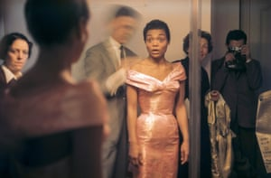 American actress and singer Eartha Kitt looks at her reflection in a full-length mirror as French fashion designer Hubert de Givenchy adjusts her dress during a fitting, Paris, France, 1961