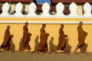 Buddhist monks parade barefoot in front of the Royal Palace in Phnom Penh