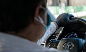 A rideshare driver wears a mask and gloves while driving. Drivers in California are calling for more benefits.