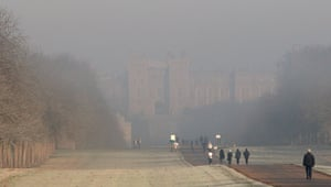 Walkers stroll along the Long Walk as fog surrounds Windsor Castle