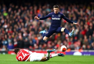Aaron Cresswell hurdles the challenge of Reiss Nelson.