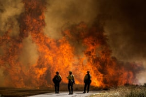 Firefighters watch as flames flare up