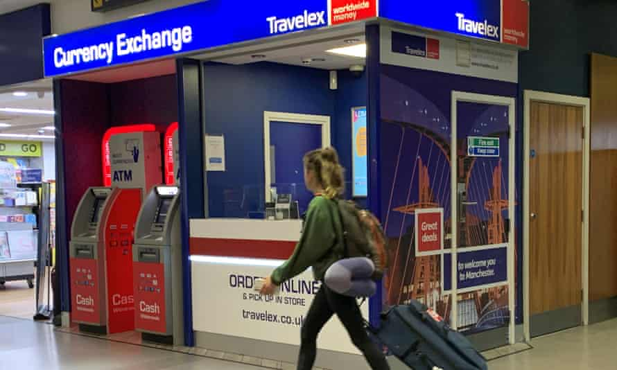 A passenger walks past a Travelex currency exchange at Manchester airport