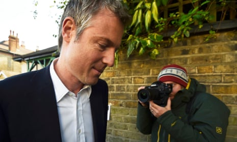 Zac Goldsmith looking sheepish and being snapped by a photographer wearing a beanie hat