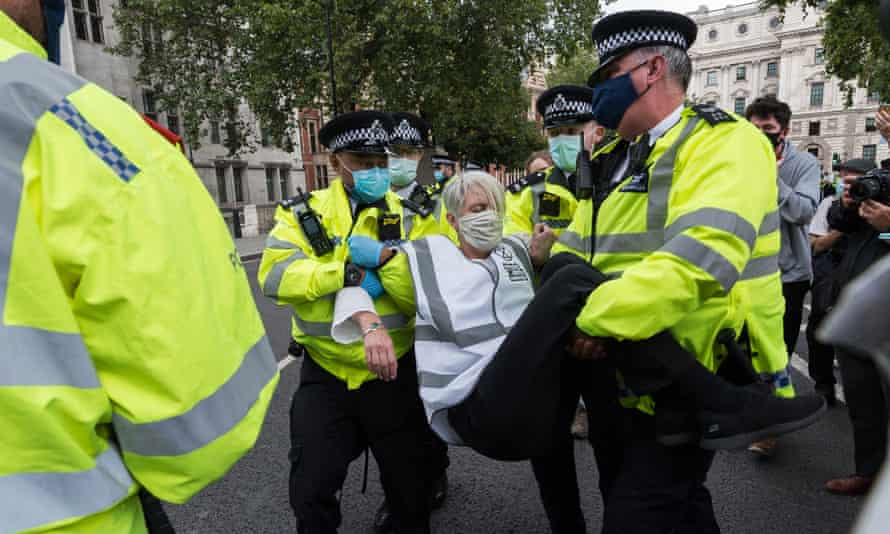 Extinction Rebellion protester being carried by three police officers