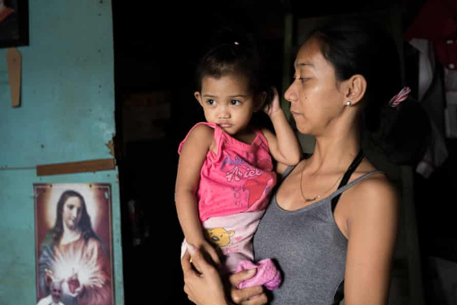 Jessica, 24 and Trista, 2 stand in their neighbours home in a Malabon City, Metro Manila, the Philippines.