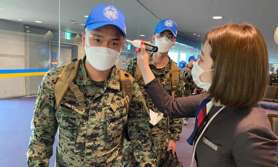South Korean peacekeeping troops are checked for fever before boarding a flight.